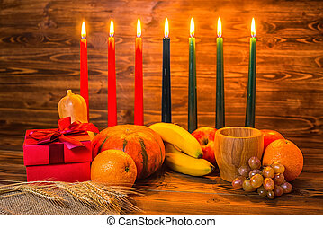 Kwanzaa holiday concept with traditional lit candles, gift box, pumpkins, ears of wheat, grapes, orange, banana, bowl and fruits on wood background