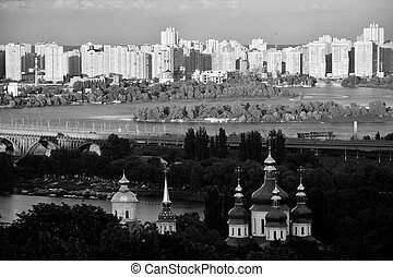 Kyiv cityscape with apartments, river, bridge and orthodox church