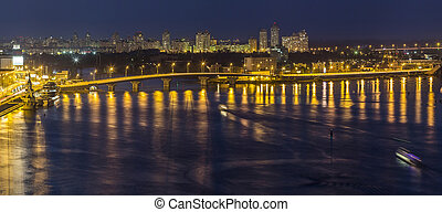Kyiv (Kiev) city, the capital of Ukraine at night beside the Dnipro (Dniepr) river with reflection in water