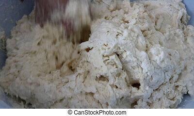 Kyrgyz woman kneads dough for lavash (round flat white...