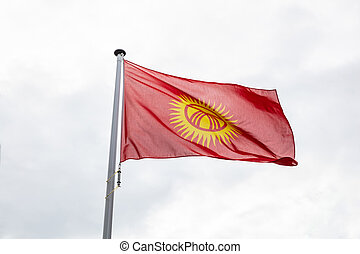 Kyrgyzstan flag on a pole waving, cloudy sky background