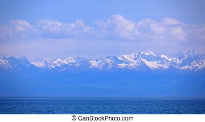 Kyrgyzstan, Issyk Kul lake and snow covered mountains. 4K telephoto lens shot