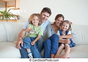 lächeln, familie, aufpassender fernsehapparat, zusammen