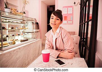 lächeln, hübsche frau, sitzen, an, der, cafeteria, und, kaffeetrinken