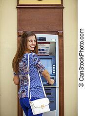 lächeln, junge frau, zurückziehen geld, von, geldautomat
