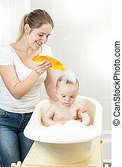 lächeln, junger, mutter, wäsche, sie, babys, kopf, mit, shampoo