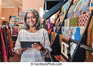 lächelnde frau, gebrauchend, a, digital tablette, in, sie, textilien, laden