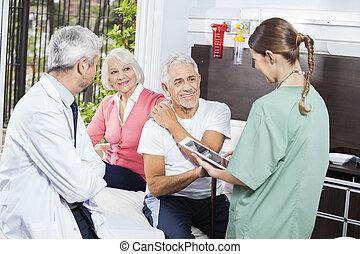 läkare, par, sittande, se, medan, kvinnlig, sköta, senior