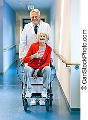 läkare, pressande, en, äldre kvinna, in, a, wheelchair.