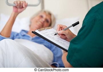 läkare skriva skrivplatta, medan, tittande vid, tålmodig
