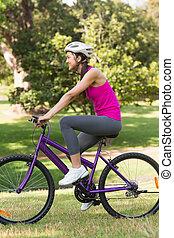 lämplig, ung kvinna, med, hjälm, ridning cykel, hos, parkera