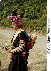 Sur la route, un couple et leur bébé va Voyage 20 km marche à la noce d'un voisin. Ils sont partis la nuit pour arriver avant midi. Si la femme a retenu les vêtements traditionnels, des hommes souvent abandonnés.