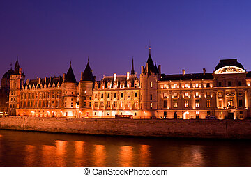 Twilight view of the Conciergerie (old medieval jailhouse) and the Seine river - Paris, France