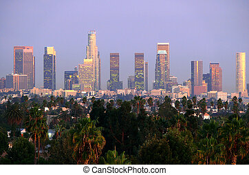 Los Angeles towers and palm trees in the post sunset afterglow.