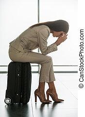 laat, voor, flight., terneergeslagen, jonge, businesswoman, in, formalwear, holdingshoofd in handen, terwijl, zittende , op, haar, koffer, in, luchthaven