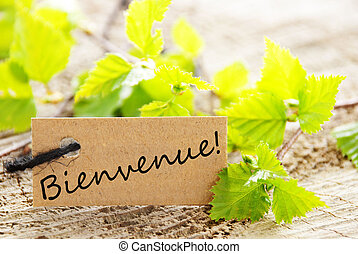 a natural looking label with green leaves and the french word bienvenue which means welcome