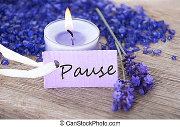 a purple label with the german word Pause which means break on it and candlelight in the background
