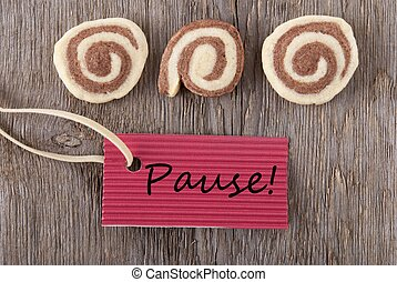 a red label with the german word Pause which means break on wooden background with cookies