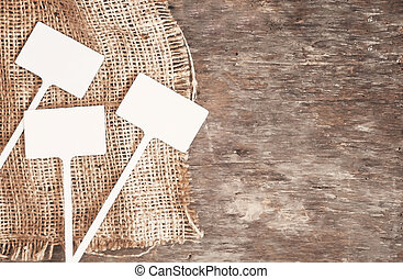 Labels-markers for plants lie on burlap, on a wooden brown background., Top view