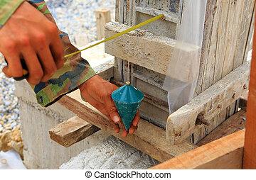 labor man using a plumb bob for check