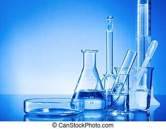 Laboratory equipment, glass flasks, pipettes on blue ...