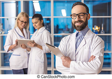 Laboratory - Handsome smiling male scientist with tablet...