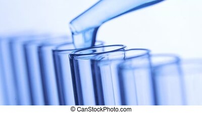 Laboratory research testing. Pipette drips drops of blue...