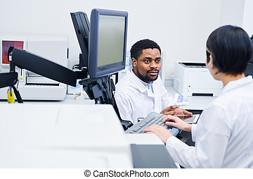 Laboratory scientists discussing results of medical tests