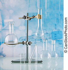 Laboratory stand with a variety of flasks and vessels on light blue background