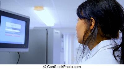 Laboratory technician using a display monitor 4k - ...