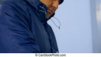 Laboratory technician wearing windcheater jacket and gloves ...