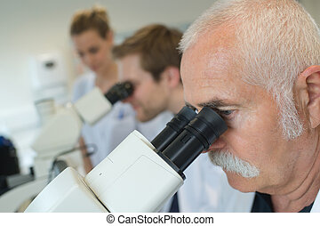 laboratory workers looking into the eyepieces of their ...