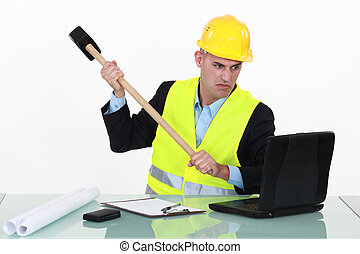 Laborer destroying computer with hammer