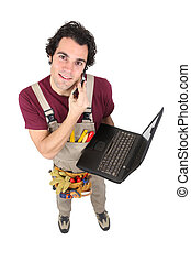 Laborer in dungarees with mobile phone and computer