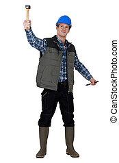 Laborer lifting hammer, studio shot