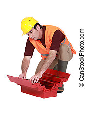 Laborer searching in  a toolbox