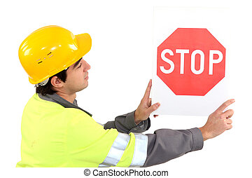 Laborer showing stop sign
