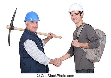 Laborer welcoming young teenage apprentice