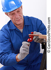 Laborer working on a copper pipe
