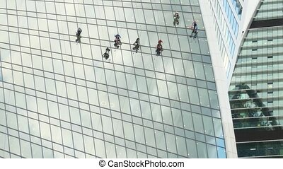 Laborers dangle high above the ground, washing the windows of an enormous, highrise building in Moscow, Russia.