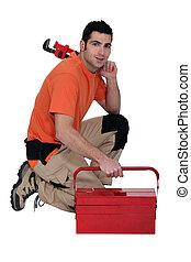 Labourer kneeling by tool box