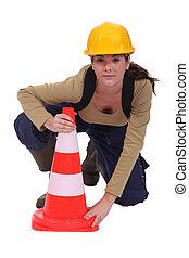 Labourer placing a traffic pylon