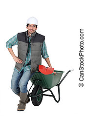 Labourer posing with a wheelbarrow and spade