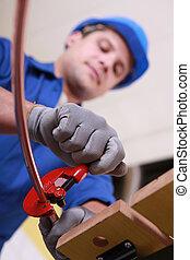Labourer using tool to prepare copper pipe