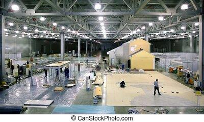 Labourers work on building site in exhibition hangar -...