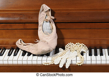 Lace glove and pearls on piano keys