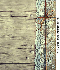 Lace, pearls, bowknot, canvas, sackcloth on wooden background. Toned.