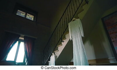 Lace wedding dress hanging in room
