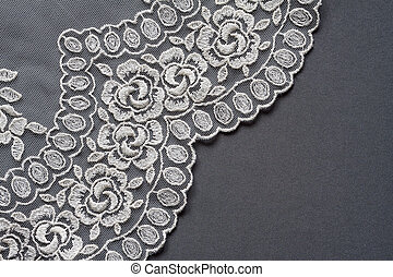 Lace. - White lace on the dark grey silk background.
