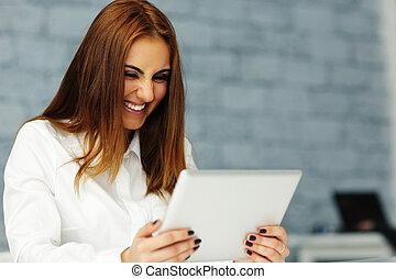 lachender, junger, geschäftsfrau, anschauen, tablette, computerbildschirm
